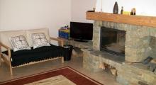 Salon z kominkiem w domku w Szczyrku